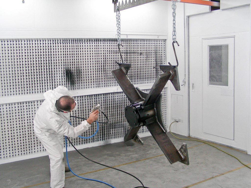 Painting application: painter is using a spray gun in spray cabin with manual conveyor