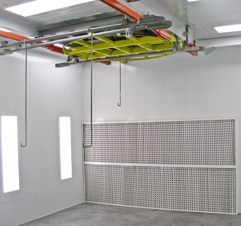 Wet paint booth with rotating station handling to turn the pieces before the spray wall