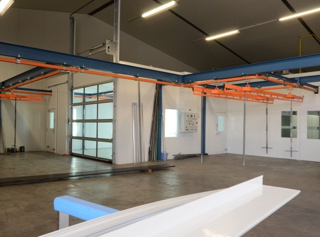 Paint area with separate heated chamber and rail system for sectional garage doors