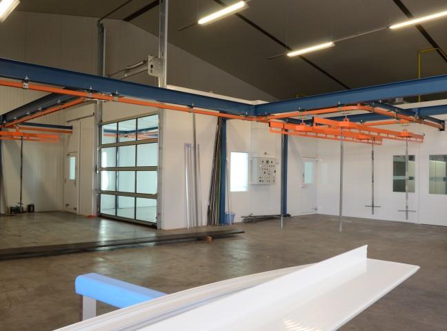 Schilderafdeling met aparte droogcabine en railsysteem voor garagesectionaalpoorten