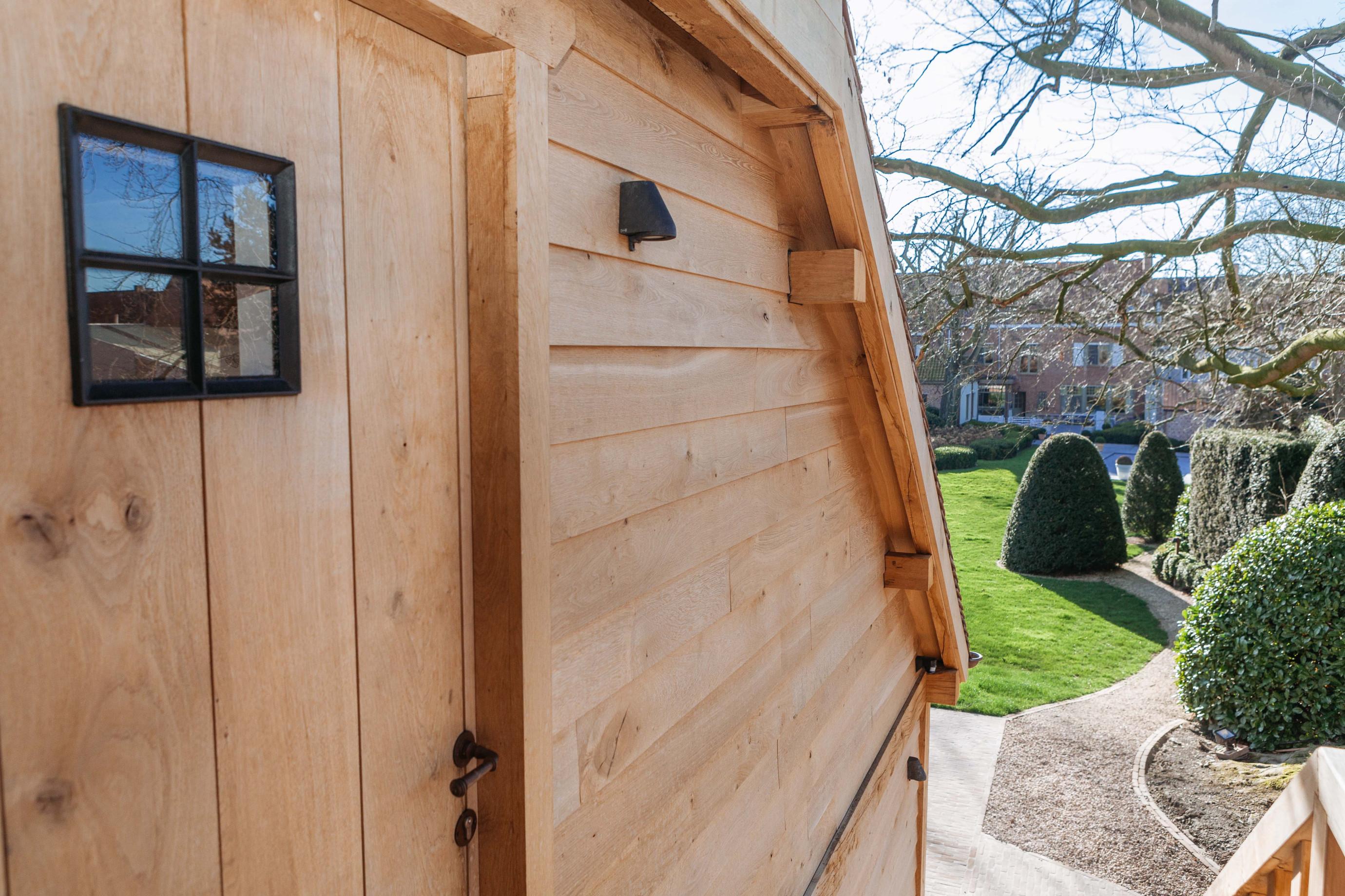 Deze eiken wand behoort tot een rustieke eiken carport met guesthouse. Dit eikenhouten bijgebouw werd gerealiseerd door Vanhauwood. Voor de opbouw van de structuur maakten ze gebruik van een op maat gemaakt eiken bouwpakket van Cornelis Hout.
