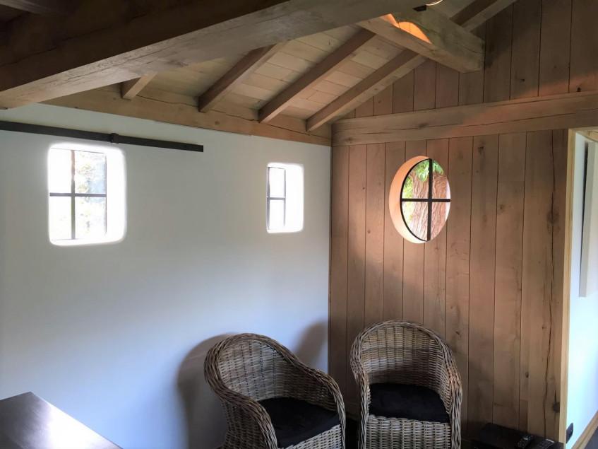 Het interieur van dit eiken bijgebouw werd afgewerkt met een stalen raam en eiken wanden. Dit houten bijgebouw werd deskundig gerealiseerd door Vanhauwood. Voor de opbouw van het eiken bijgebouw werd gebruik gemaakt van een op maat gemaakt eiken bouwpakket vervaardigd door Cornelis Hout.