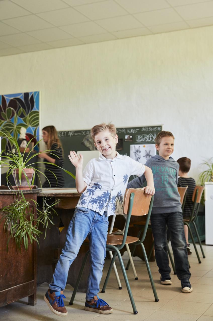 Twee kindjes staan recht naast stoel en ene kind zwaait naar camera