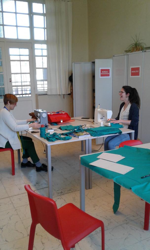 Twee jonge vrouwen maken mondmaskers met naaimachine