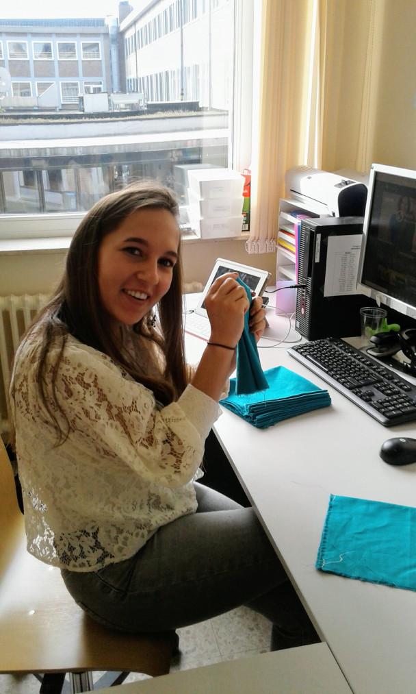 Jonge vrouw sorteert groene stoffen om mondmaskers te maken
