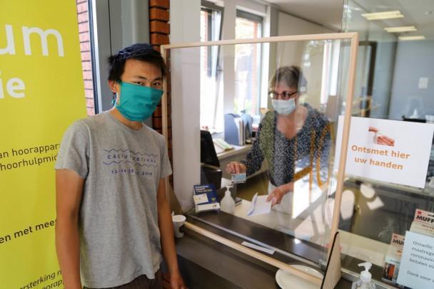 Jonge man met mondmasker geeft brief via plexi aan vrouw