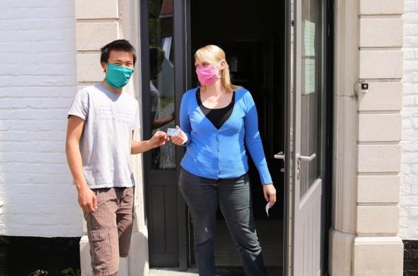 Begeleidster met roze mondmasker ontvangt post van jonge man met mondmasker