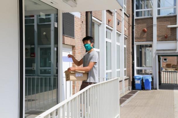 Jonge man met mondmasker levert post af