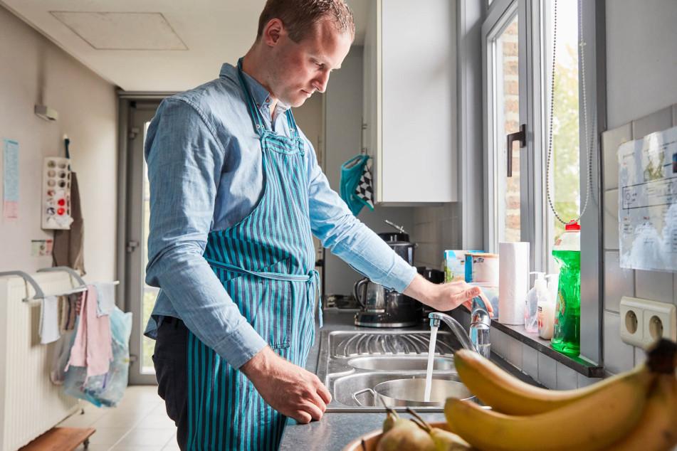 Jonge man met beperking staat in keuken met schort aan