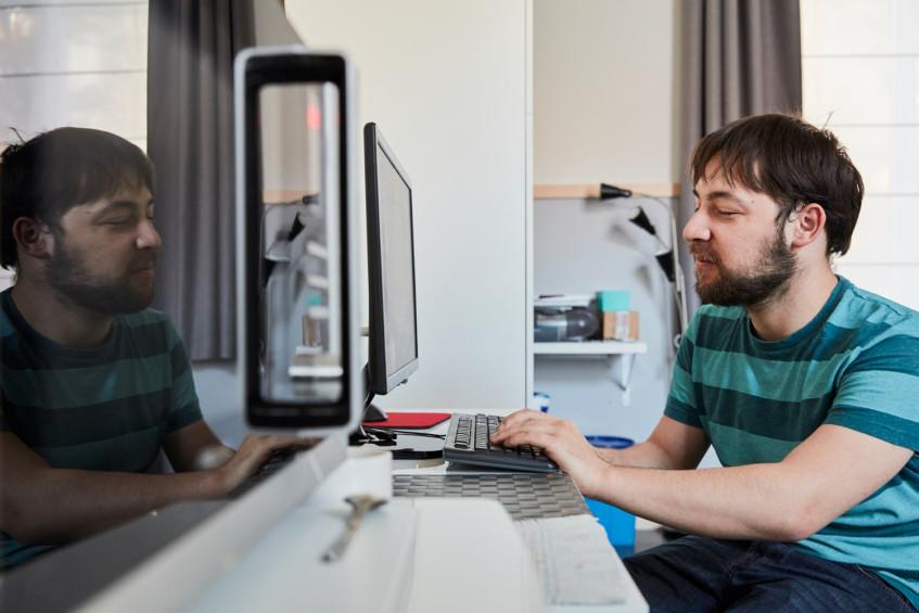 Slechtziende man met gestreepte T-shirt bezig aan computer